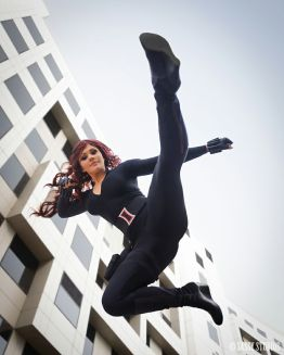 An accrobatic cosplayer depicting Black Widow in action